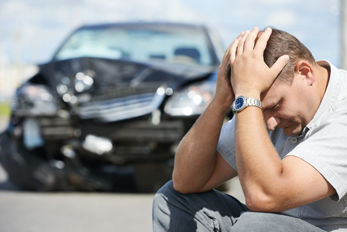 Man sitting down with hands on head with damaged car in the background